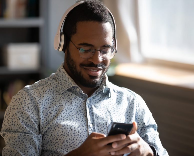 African,Man,Wear,Headphones,Holds,Cellphone,Choose,Track,Listens,Digital